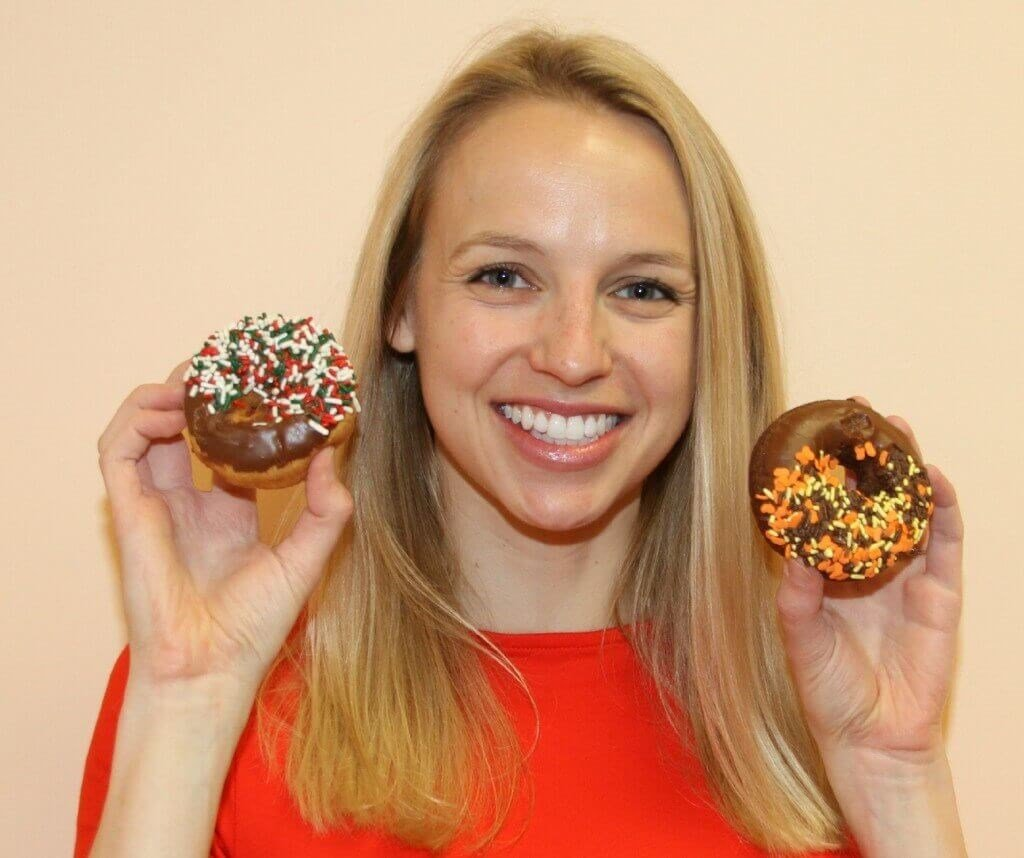A woman holding two donuts represents a play on words for donut mastopexy.