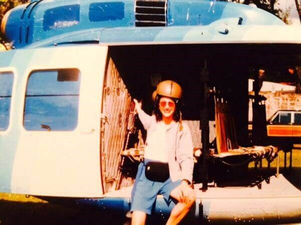 Dr. Heather Furnas leaning against a helicopter wearing a helmet on R & R Day after Plastic Sgery Cleft Lip and Palate Mission
