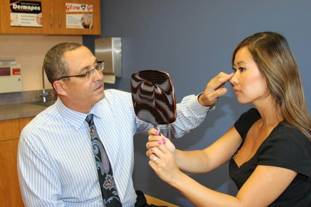 A plastic surgeon explains a procedure to a patient.