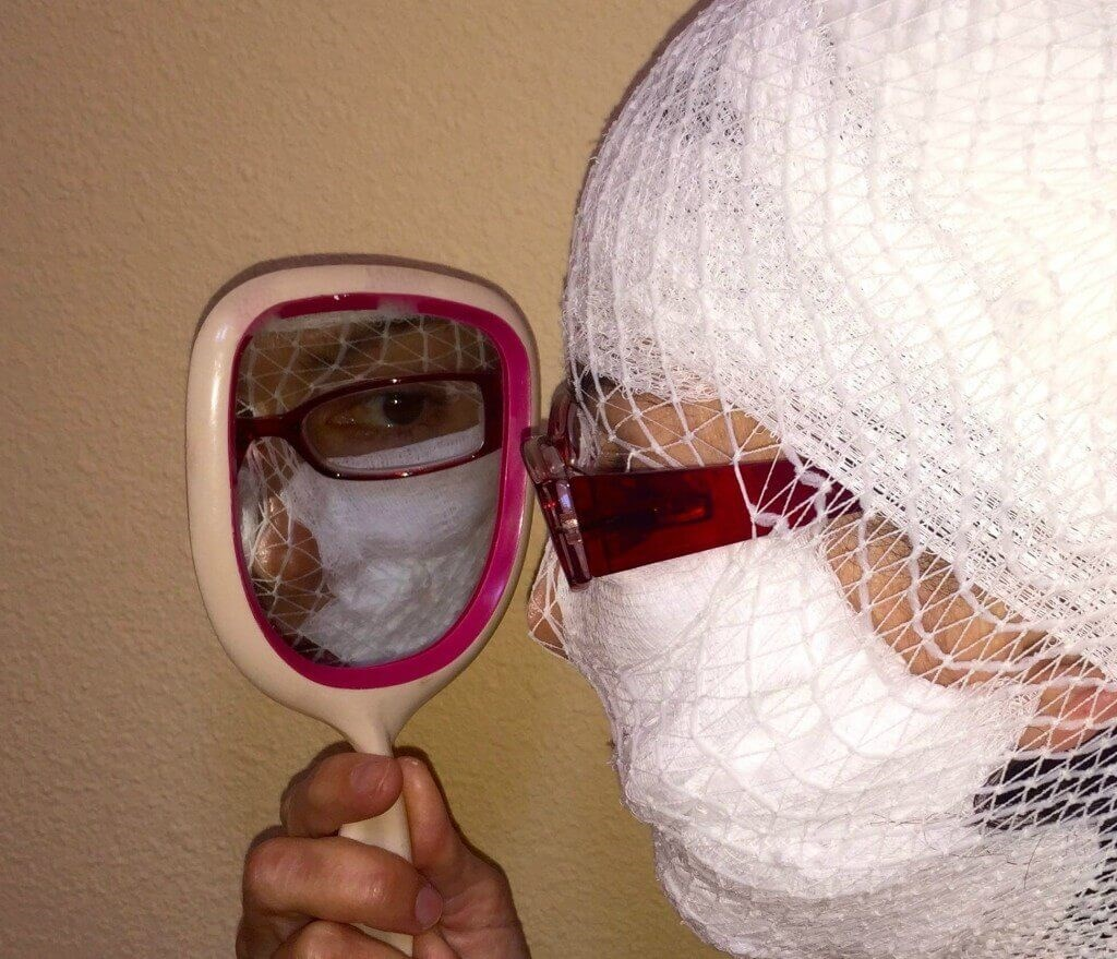 A plastic surgery patient in head and face bandages scrutinizes herself looking in a mirror with reading glasses