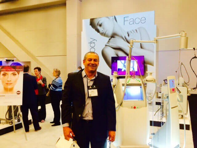 Francisco Canales, MD standing next to UltraShape machine in Exhibit Hall