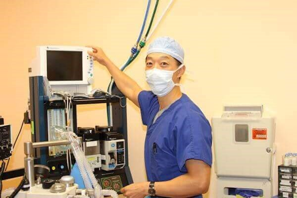 Anesthesiologist attending to a plastic surgery patient in an accredited operating room.