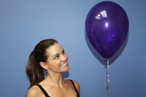 Woman smiling at a purple balloon