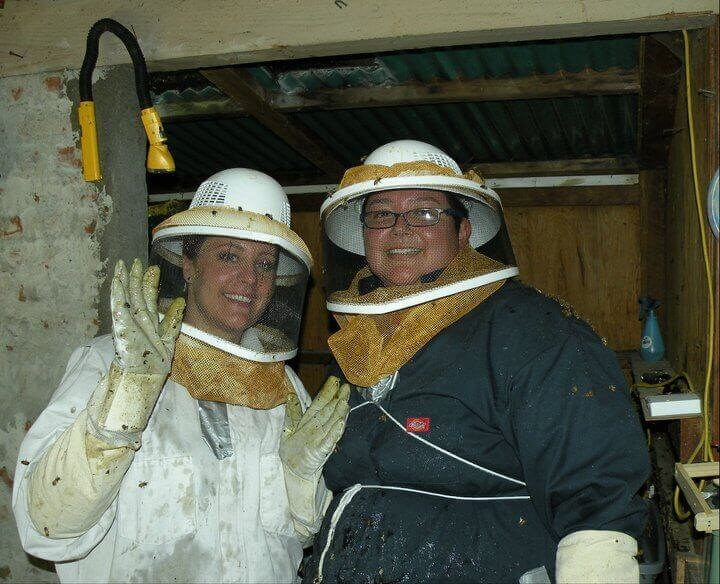 Raquel and Leah, the Beekeepers in their beekeeper suits