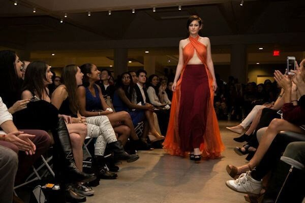 Siena on runway in orange and burgundy evening dress for Harvard's Identities Fashion Show